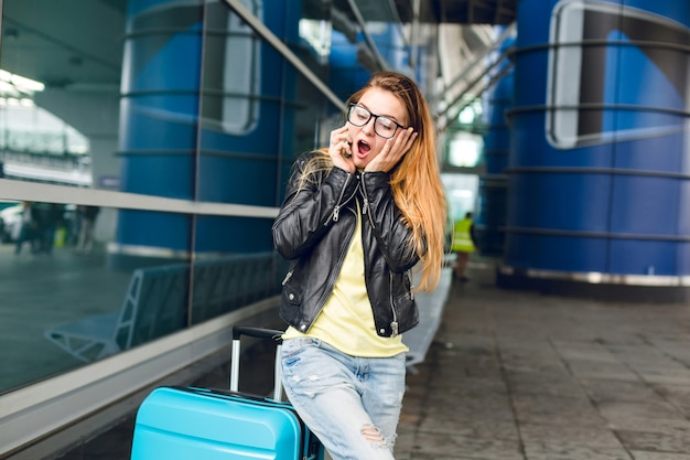 Jong meisje met lang haar in zwarte jas staat in de buurt van koffer buiten op de luchthaven. ze heeft lang haar, een zwarte bril. geïntrigeerd telefoneren.