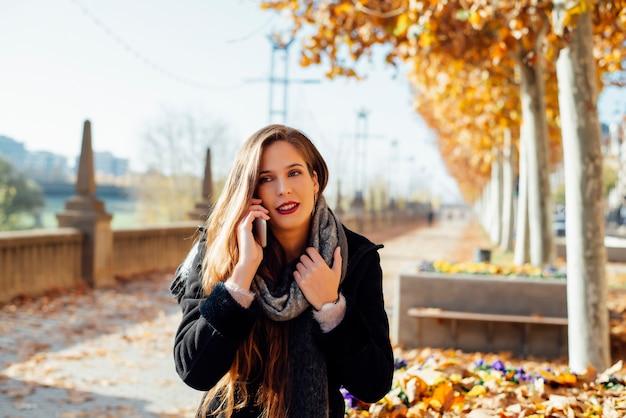 Jong meisje met lang haar spreekt aan de telefoon tijdens een wandeling in het park in de herfst.