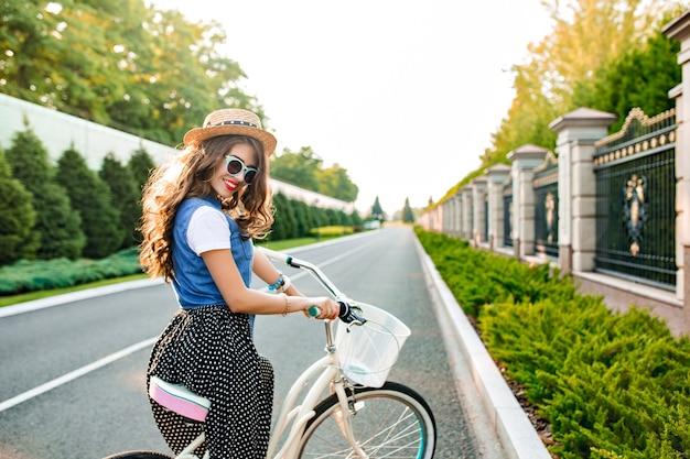 Jong meisje met lang krullend haar in blauwe zonnebril gaat met de fiets op weg. ze draagt een lange rok, jerkin, hoed. zij lacht. uitzicht vanaf de achterkant.