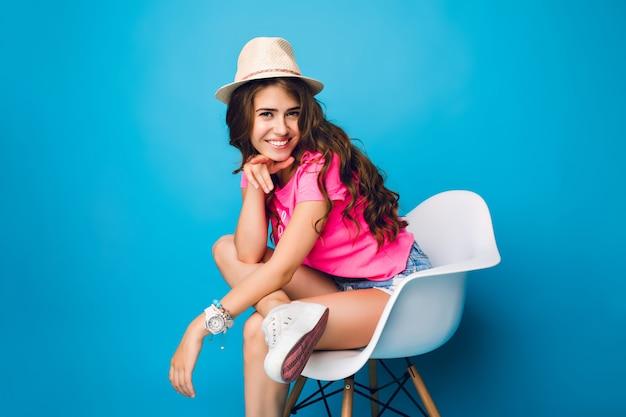 Jong meisje met lang krullend haar in hoed is poseren in stoel op blauwe achtergrond in de studio. ze draagt een korte broek, een roze t-shirt, witte sneakers. ze houdt haar been op de knie en lacht naar de camera.