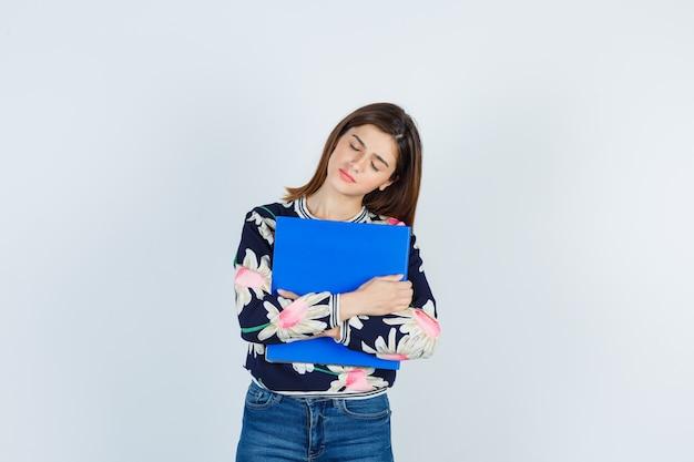 Jong meisje met map, ogen sluiten in bloemenblouse, jeans en er moe uitzien, vooraanzicht.