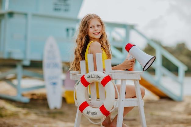 Jong meisje met megafoon zittend op de badmeesterstoel op het strand the