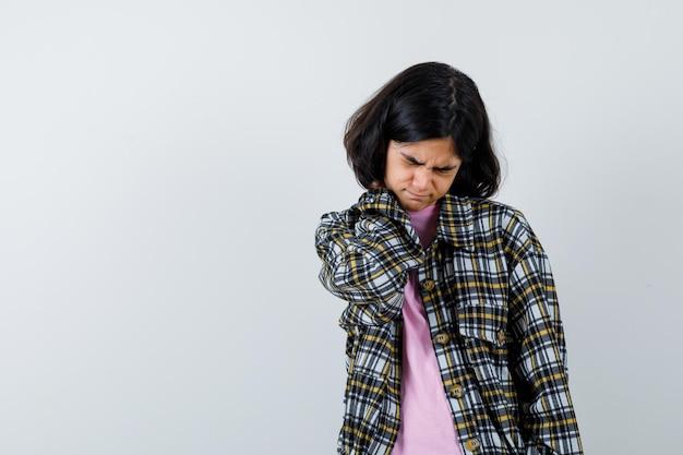 Jong meisje met nekpijn in geruit overhemd en roze t-shirt en ziet er uitgeput uit. vooraanzicht.