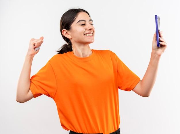 Jong meisje met oranje t-shirt met smartphone gebalde vuist blij en opgewonden staande op witte achtergrond