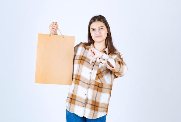 Jong meisje met papieren ambachtelijke pakket en duimen naar beneden geven over witte muur.