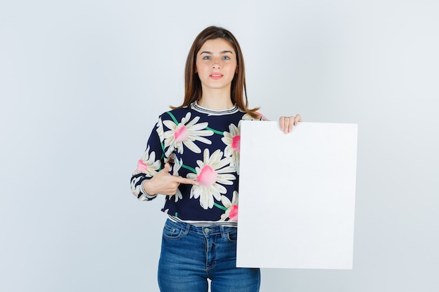 Jong meisje met papieren poster in bloemenblouse, jeans en verbaasd, vooraanzicht.