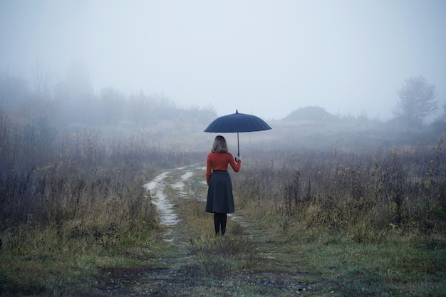 Jong meisje met paraplu in herfst veld