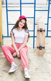 Jong meisje met pet zittend naast skateboard
