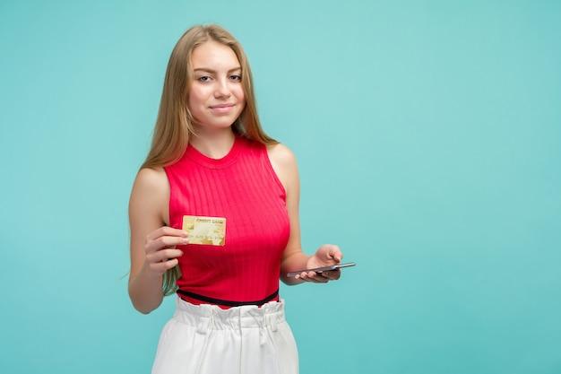 Jong meisje met plastic creditcard terwijl mobiele telefoon geïsoleerd op blauwe achtergrond