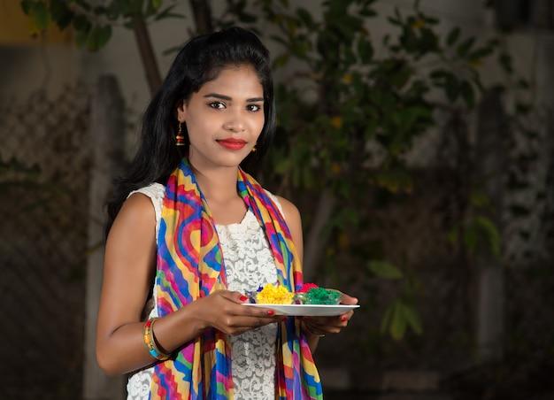 Jong meisje met poederkleuren in plaat op het kleurenfestival genaamd holi, een populair hindoefestival dat in heel india wordt gevierd