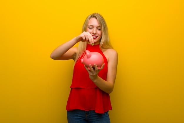Jong meisje met rode kleding over gele muur die een spaarvarken neemt en gelukkig omdat het hoogtepunt is