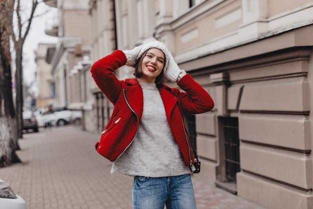 Jong meisje met rode lippenstift lacht en zet op gebreide muts. vrouw in stijlvolle jas en spijkerbroek wandelingen in herfst stad.