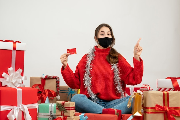 Jong meisje met rode trui en zwart masker met kaart wijzend op iets rondhangen presenteert op wit
