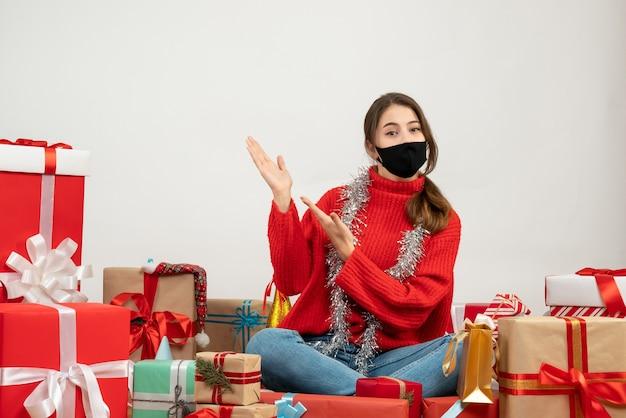 Jong meisje met rode trui en zwart masker wijzend op iets rondhangen presenteert op wit