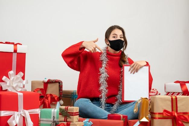 Jong meisje met rode trui met documenten rondhangen presenteert met zwart masker op wit