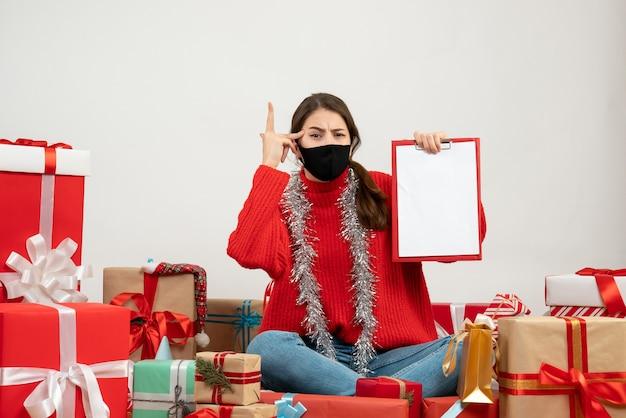 Jong meisje met rode trui met documenten zitten presenteert op wit