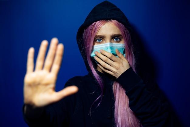 Jong meisje met roze haar en blauwe ogen, die medisch griepmasker en hooded sweater dragen, die stop-gebaar op muur van spookblauwe kleur tonen.