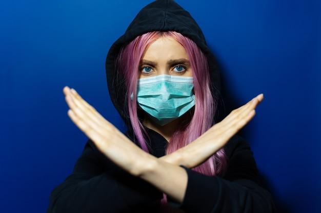 Jong meisje met roze haar en blauwe ogen, die medisch griepmasker en sweater met een kap dragen, geen gebaar op muur van spookblauwe kleur tonen.