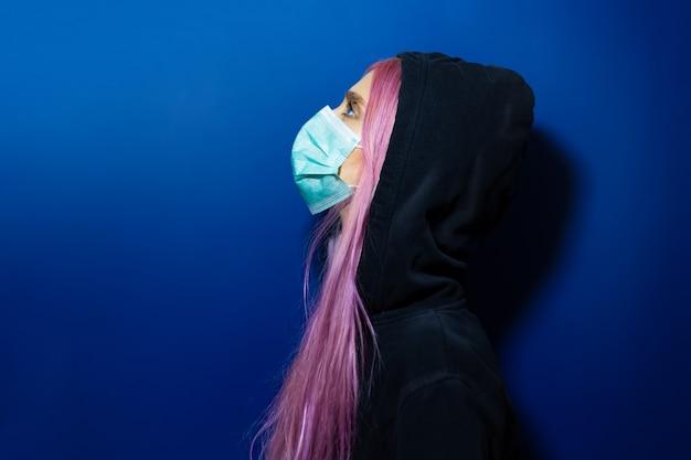 Jong meisje met roze haar en blauwe ogen, die medisch griepmasker en sweater met een kap dragen, omhoog kijkend, op muur van fantoomblauwe kleur.