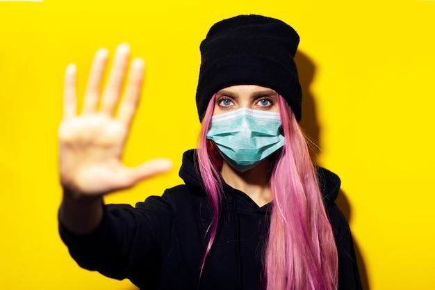 Jong meisje met roze haar en blauwe ogen, die medisch griepmasker, trui met capuchon en beanie-hoed draagt, stopgebaar op gele muur toont.