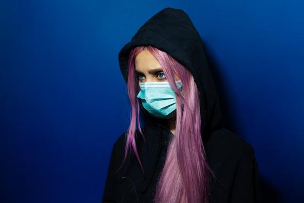Jong meisje met roze haar en blauwe ogen, medisch griepmasker en hooded sweater dragen op muur van fantoom blauwe kleur.