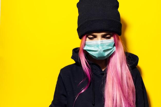 Jong meisje met roze haar en blauwe ogen, met medisch griepmasker, gekleed in zwarte hoodiesweater en beanie-hoed op gele muur.