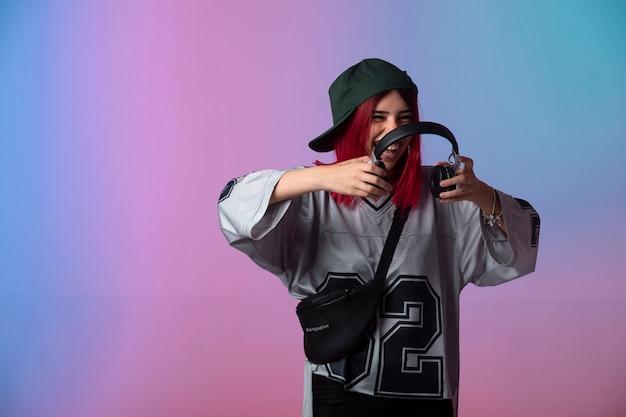 Jong meisje met roze haren hoofdtelefoon dragen.