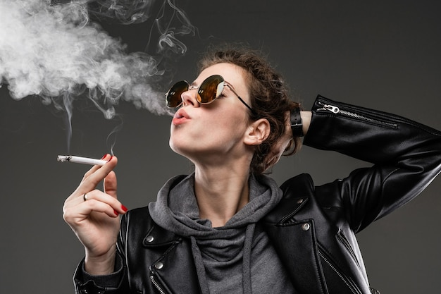 Jong meisje met ruwe gelaatstrekken in zwarte jas rookt geïsoleerd