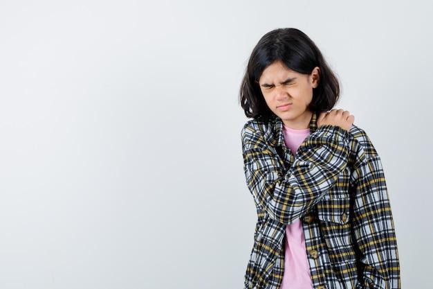Jong meisje met schouderpijn in geruit overhemd en roze t-shirt en ziet er uitgeput uit. vooraanzicht.