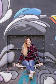 Jong meisje met skateboard in een graftiti muur