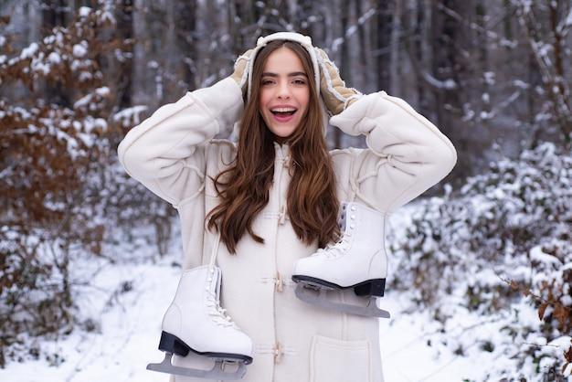Jong meisje met skateshoes op haar schouders in winter woud