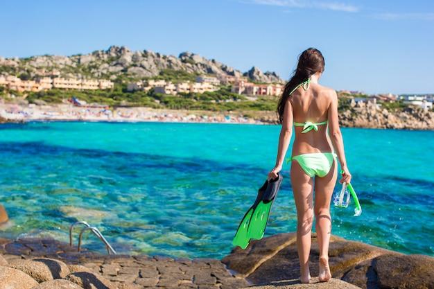 Jong meisje met snorkeluitrusting op grote stenen klaar om te zwemmen