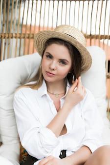 Jong meisje met strohoed die in een schommelingsstoel op het terras van haar huis rust