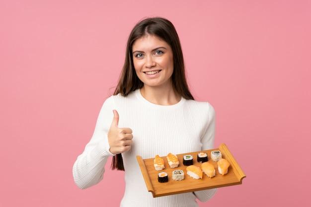 Jong meisje met sushi over geïsoleerd roze met omhoog duimen omdat iets goeds is gebeurd