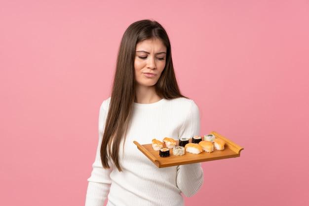 Jong meisje met sushi over geïsoleerde roze achtergrond met droevige uitdrukking