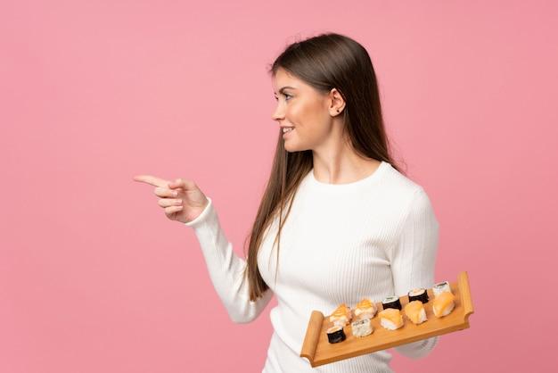 Jong meisje met sushi over geïsoleerde roze muur die aan de kant richt om een product te presenteren