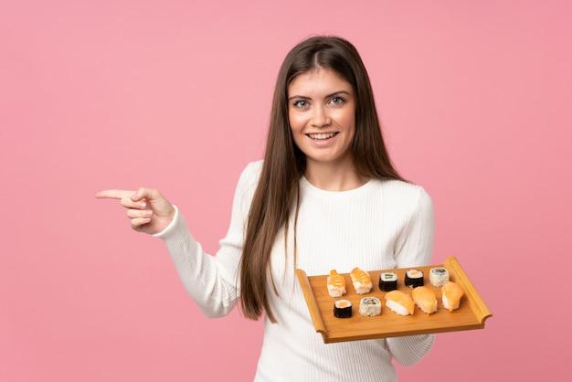 Jong meisje met sushi over geïsoleerde roze verrast en wijzende vinger aan de kant