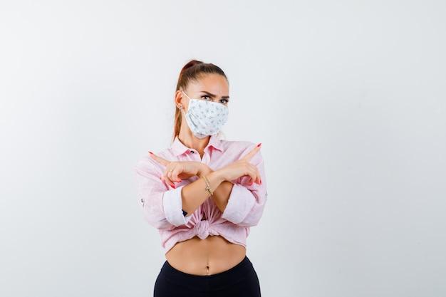 Jong meisje met twee gekruiste armen, wijzend in tegengestelde richtingen in roze blouse, zwarte broek, masker en op zoek verleidelijk, vooraanzicht.