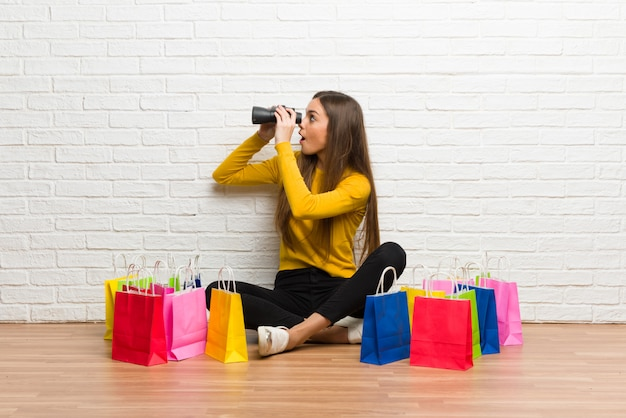 Jong meisje met veel boodschappentassen en kijken in de verte met een verrekijker