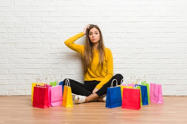 Jong meisje met veel boodschappentassen met een uitdrukking van frustratie en niet begripvol