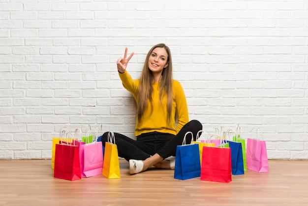 Jong meisje met veel het winkelen zakken die en overwinningsteken glimlachen tonen
