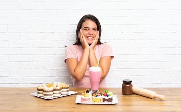 Jong meisje met veel verschillende minicakes met verrassingsgelaatsuitdrukking
