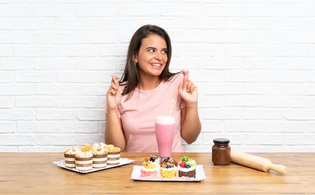 Jong meisje met veel verschillende minicakes met vingers kruising