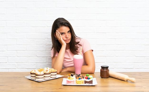 Jong meisje met veel verschillende minicakes ongelukkig en gefrustreerd