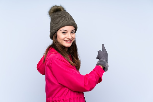 Jong meisje met winter hoed op blauw terug te wijzen