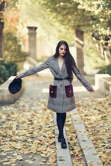 Jong meisje met zeer lang haar die de winterlaag en glb in stedelijk parkhoogtepunt dragen van de herfstbladeren