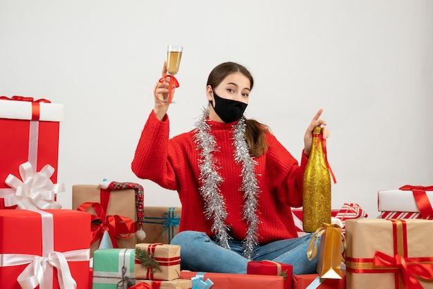 Jong meisje met zwart masker champagne fles houden en roosteren rond cadeautjes op wit