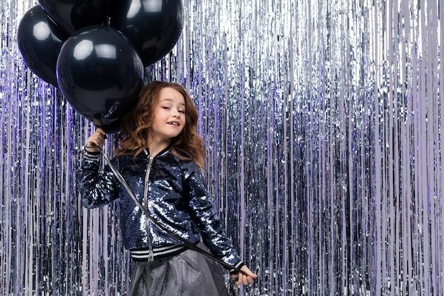 Jong meisje met zwarte helium ballonnen op een glanzende vakantie muur