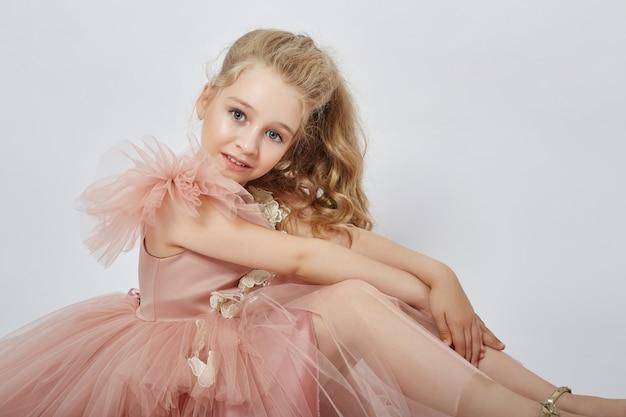 Jong meisje missen schoonheid in een mooie jurk. cosmetica en make-up voor kinderen. meisje poseren op een lichte muur. grappige emoties en verrassing.