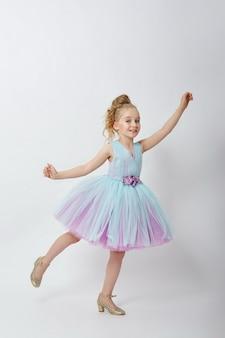 Jong meisje missen schoonheid in een mooie jurk. kindercosmetica en make-up. meisje poseren op een lichte achtergrond. grappige emoties en verrassing. rusland, sverdlovsk, 23 juni 2019